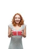 Młody miedzianowłosy szczęśliwy uśmiechnięty dziewczyny mienia prezent Zdjęcie Royalty Free