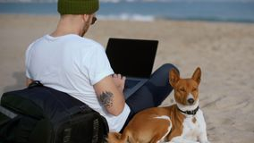 Młody millennial mężczyzna z najlepszego przyjaciela psem przy plażą zbiory wideo