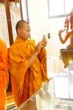 Młody mnich buddyjski sprawdza telefon komórkowego Zdjęcia Royalty Free