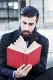Młody modniś czyta książkowego obsiadanie outdoors Zdjęcia Stock