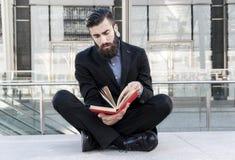 Młody modniś czyta książkowego obsiadanie outdoors Fotografia Stock