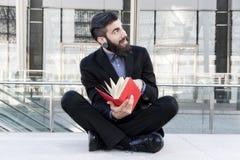Młody modniś czyta książkowego obsiadanie outdoors Obrazy Stock