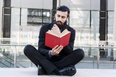 Młody modniś czyta książkowego obsiadanie outdoors Fotografia Royalty Free