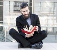Młody modniś czyta książkowego obsiadanie outdoors Zdjęcia Royalty Free
