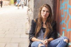 Młody modniś dziewczyny obsiadanie na ulicie Problemu nastolatek fotografia stock