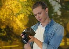 młody modnisia fotograf patrzeje fotografie na kamerze, w parku bokeh nasunięcie Obraz Royalty Free