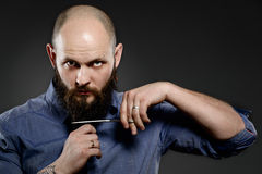 Młody modnisia mężczyzna ciie jego brodę z nożycami - popielaty tło Obraz Royalty Free
