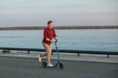 Młody modnisia mężczyzna, jedzie na kopnięcie hulajnoga po pracy na zmierzchu Pojęcie zdrowy wisząca ozdoba transport Fotografia Royalty Free