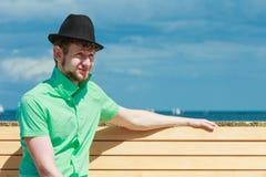 Młody modnisia mężczyzna obsiadanie na ławce blisko morza plenerowego Obrazy Stock