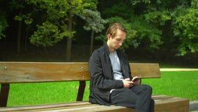 Młody modnisia mężczyzna use smartphone i odpoczynek w parku zbiory