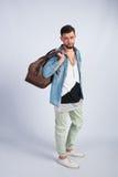 Młody modny facet w studiu jest podróży torbą Obrazy Stock
