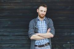 Młody modny mężczyzna przeciw drewnianej ścianie Obrazy Stock