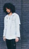 Młody murzyn z afro włosy pozuje na grafitowym tle _ Ubierający w cajg kurtce, czarni spodnia Zdjęcia Stock