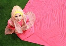 Młody muzułmański dziewczyny obsiadanie na trawie Fotografia Royalty Free