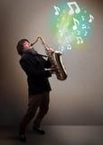 Młody muzyk bawić się na saksofonie podczas gdy muzykalnych notatek explodin Obrazy Stock