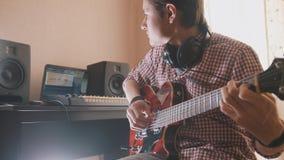 Młody muzyk komponuje ścieżkę dźwiękowa bawić się gitarę i nagrywa używać komputer, hełmofony i klawiaturę, fotografia royalty free