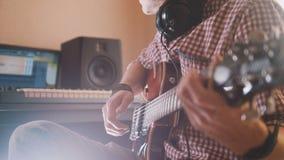 Młody muzyk komponuje ścieżkę dźwiękowa bawić się gitarę i nagrywa używać komputer i klawiaturę zdjęcie royalty free