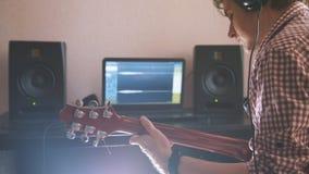 Młody muzyk komponuje muzykę bawić się gitarę elektryczną i nagrywa używać komputer i klawiaturę fotografia royalty free