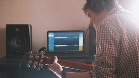 Młody muzyk komponuje muzykę bawić się gitarę elektryczną i nagrywa używać komputer i klawiaturę zdjęcia royalty free