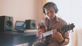 Młody muzyk komponuje muzykę bawić się gitarę i nagrywa używać komputer obrazy royalty free