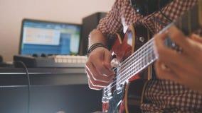 Młody muzyk komponuje muzykę bawić się gitarę i nagrywa używać komputer i klawiaturę fotografia royalty free