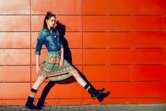 Młody nastolatek dziewczyny pozować, iść, bieg blisko miastowego czerwieni ściany tła w spódnicie i cajg kurtka na zmierzchu, zdjęcie stock