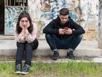 Młody nastoletni chłopak opowiada na telefonie komórkowym i ignoruje g obraz royalty free