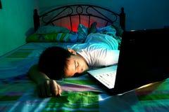 Młody Nastoletni dosypianie przód laptop na łóżku i Zdjęcia Stock