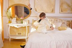 Młody nastoletni facet jest ubranym białego lying on the beach na łóżku w i garnitur pokoju, rozciąganiu i ziewaniu jego Złotych, obraz stock