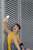 Młody nastoletni używać jego outdoors i robić selfie telefon zdjęcie stock