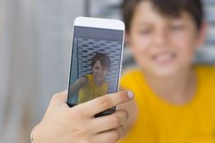 Młody nastoletni używać jego outdoors i robić selfie telefon fotografia stock