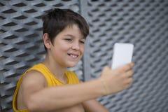 Młody nastoletni używać jego outdoors telefon fotografia royalty free