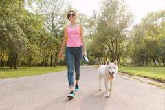 Młody nastoletniej dziewczyny odprowadzenie z psem w parku zdjęcie stock