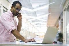 Młody nauczyciel i uczeń na pracowniku opowiada na telefonie przez laptopu łączyliśmy sieć bezprzewodowa Obrazy Royalty Free