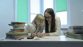 Młody nauczyciel jest usytuowanym na stole i opowiada uczennica w szkłach zbiory