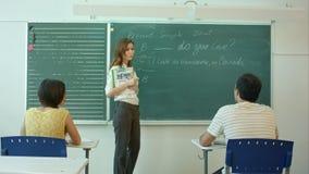 Młody nauczyciel opowiada grupować blisko chalkboard w szkolnej sala lekcyjnej zbiory