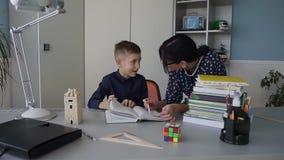 Młody nauczyciel uczy szkoła podstawowa ucznia czytać książkę dobrze homework Wyjaśniać pracę domową zbiory