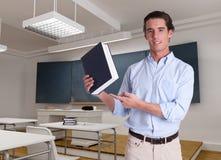 Młody nauczyciel wskazuje książka zdjęcia stock