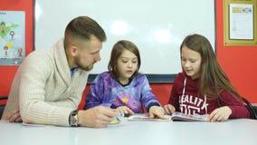 Młody nauczyciel wyjaśnia nauczanie materiału dwa uczennicy zdjęcie wideo