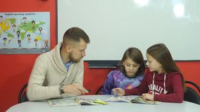 Młody nauczyciel wyjaśnia nauczanie materiału dwa uczennicy zbiory