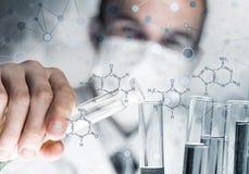 Młody naukowiec miesza odczynniki w szklanej kolbie w klinicznym laboratorium zdjęcia stock