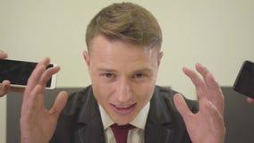 Młody nerwowy zaakcentowany ruchliwie mężczyzna stawia telefony komórkowych jego w formalnej odzieży obsiadaniu w biurze podczas  zdjęcie wideo