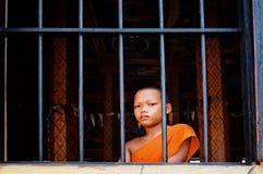 młody nowicjusza mnicha buddyjskiego zerkanie patrzeje outside okno od jego monasteru obraz stock