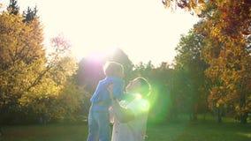 Młody ojciec bawi się z dzieckiem, trzymając go w ramionach, rzuca Promienie słońca przez dziecko Śmiech zbiory