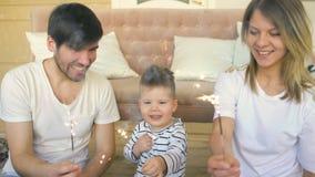 Młody ojciec i matka świętuje ich synów urodzinowych płonących sparklers i ono uśmiecha się w domu zdjęcie wideo