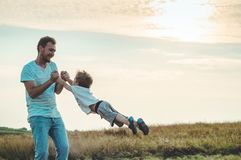 Młody ojciec rzuca jego młodego syna w wieczór świetle słonecznym dzień ojciec s Ojcuje trzymać jego małego syna, wiruje on Jesie obrazy royalty free