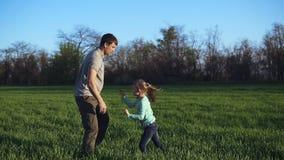 Młody ojciec z córką błaź się wokoło w otwartej wsi Mężczyzna rzuca dziewczyny w powietrzu, łaskocze ona, mieć zbiory