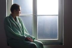 Młody pacjent z nowotworem obsiadanie przed szpitalnym okno obrazy stock