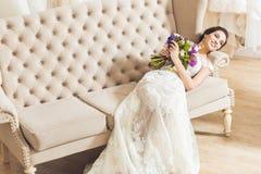 Młody panny młodej lying on the beach na kanapie z kwiatu bukietem fotografia stock