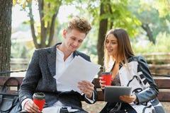 Młody partnera biznesowego spojrzenie przez ich dokumentów i siedzi na ławce w ulicie obrazy royalty free